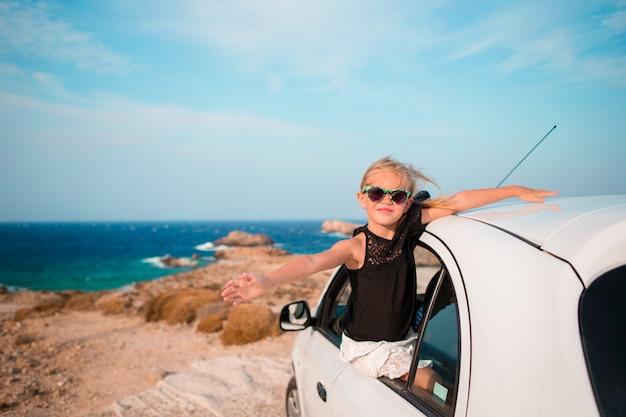 バカンスの小さな女の子が車で旅行します。美しい風景