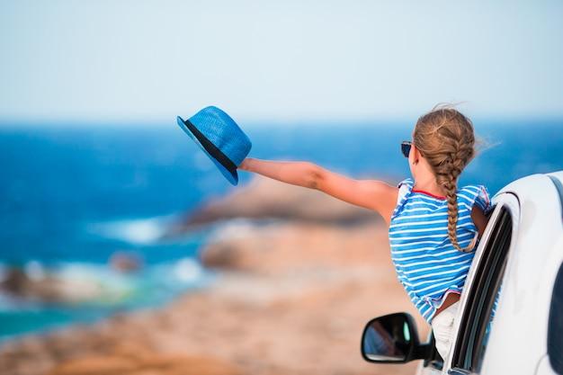 休暇の女の子が美しい景色を車で旅行します。