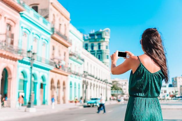 Туристическая женщина в популярном районе в гаване, куба. молодая женщина путешественник улыбается счастливым.