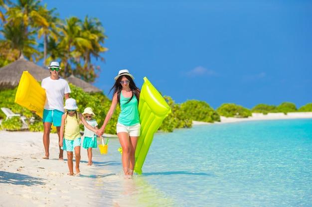 Молодая семья из четырех человек на пляжном отдыхе