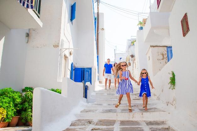 Отец и дети на узкой улице на острове миконос, в греции