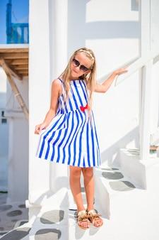ギリシャのミコノス島の典型的なギリシャの伝統的な村の通りに青いドレスでかわいい女の子