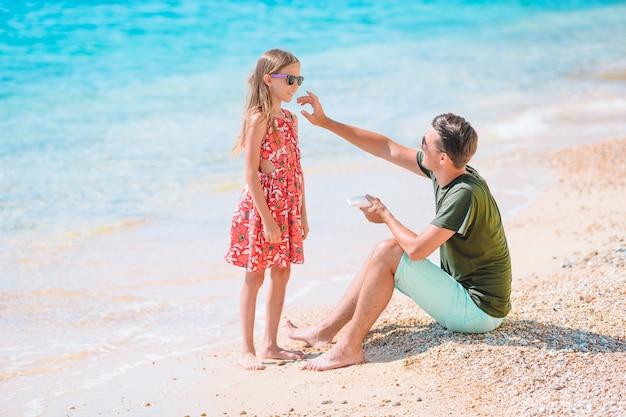 Молодой папа, применяя солнцезащитный крем для дочери нос на пляже. защита от солнца