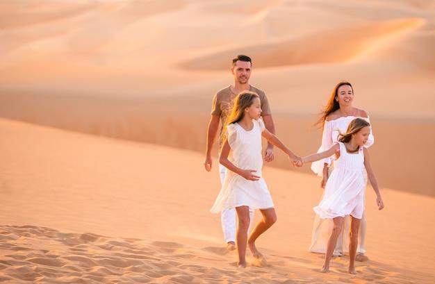 Молодая семья из четырех человек в большой песчаной пустыне