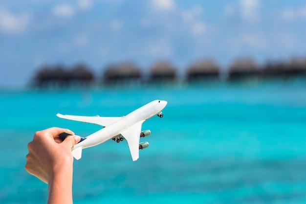 熱帯のビーチのウォーターバンガローに小さな白いおもちゃの飛行機