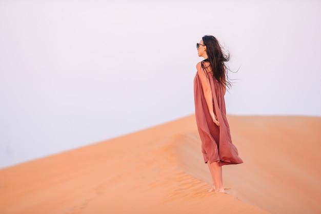 アラブ首長国連邦の砂漠の砂丘の中で少女