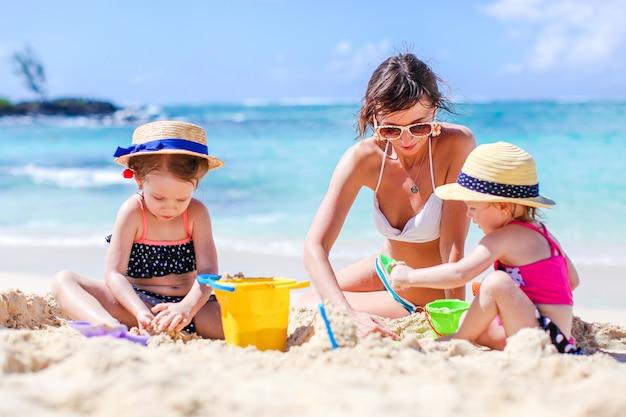 Мать и маленькие дочери, делая замок из песка на тропическом пляже