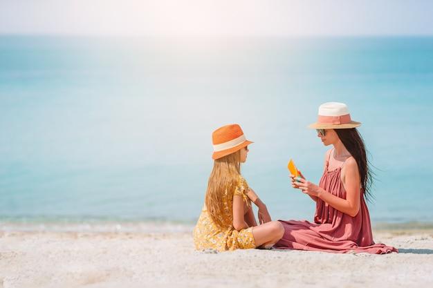 Молодая мать, применяя солнцезащитный крем для дочери нос на пляже. защита от солнца