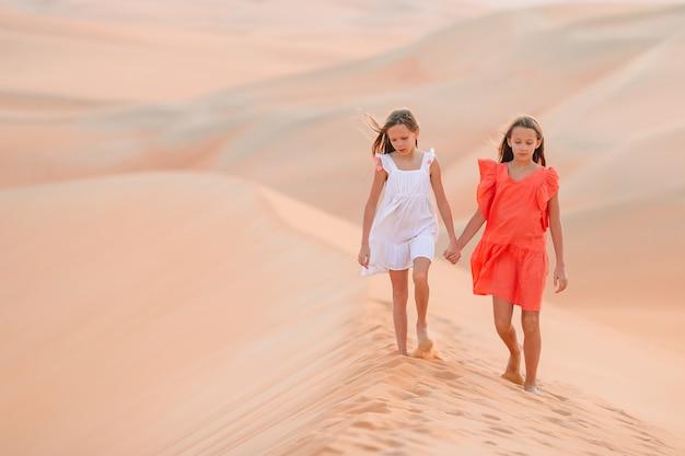 Девушки среди дюн в пустыне руб аль-хали в объединенных арабских эмиратах