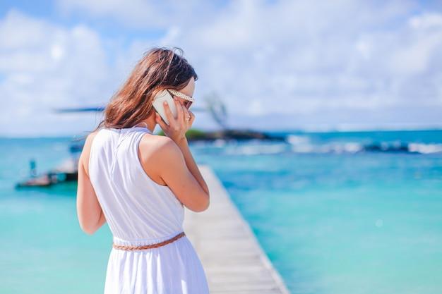 熱帯の海岸で楽しんで若い美しい女性。幸せな少女、カリブ海の島の海で青い空と青緑色の水