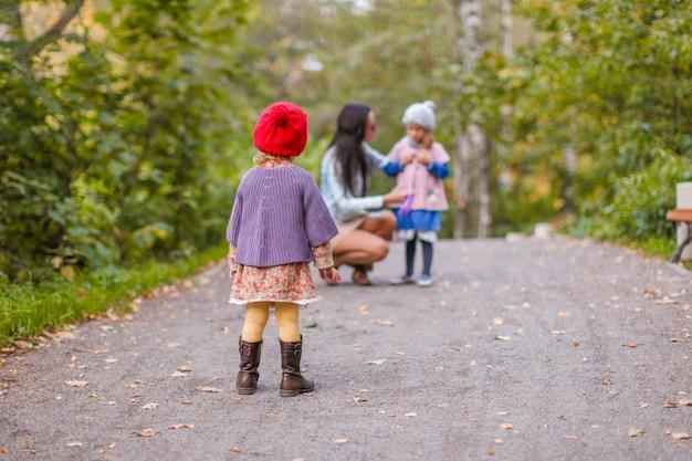 Молодая мать с ее очаровательными счастливыми дочерьми веселится на свежем воздухе в осеннем парке
