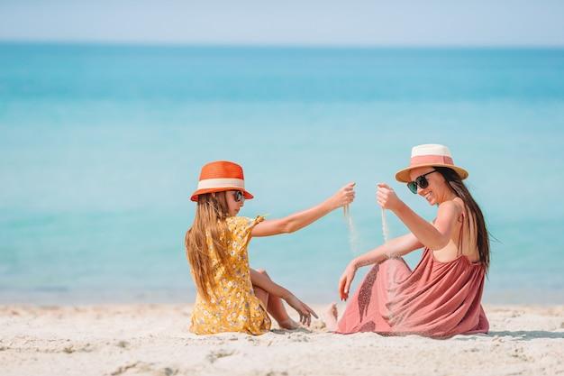 Красивая мама и дочь на пляже карибского бассейна, наслаждаясь летние каникулы