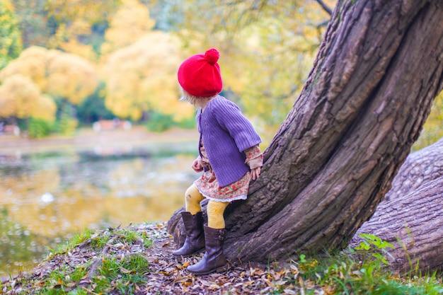 Милая маленькая девочка в красной шапочке возле озера в осенний парк