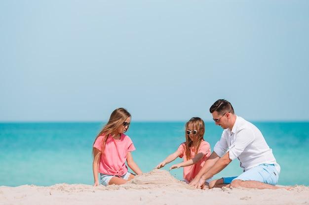 Отец и дети, делая замок из песка на тропическом пляже. семья играет с пляжными игрушками