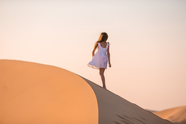 Девушка среди дюн в пустыне в объединенных арабских эмиратах