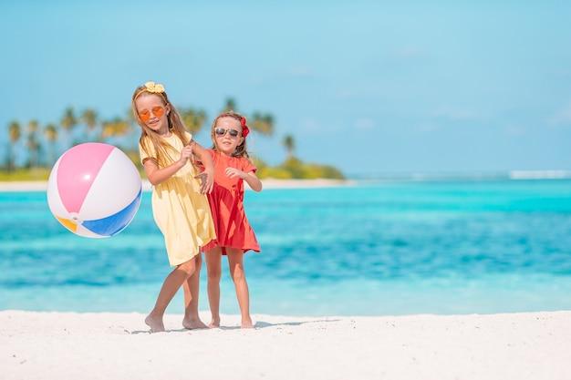 ビーチで空気球で遊ぶ愛らしい女の子。海岸で楽しい子供たち