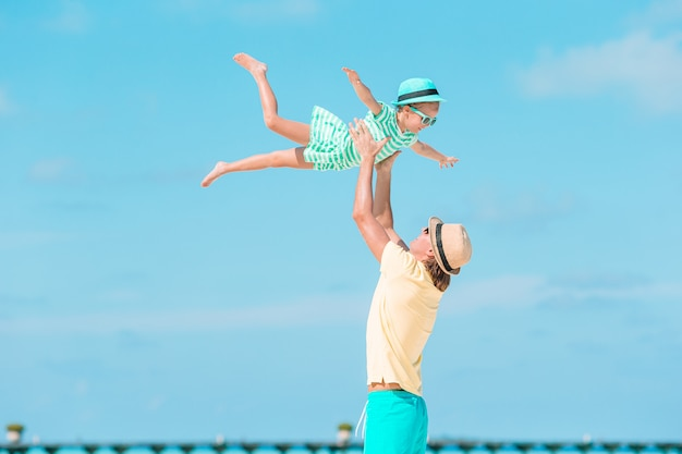 小さな女の子とビーチでの休暇中に楽しんで幸せなお父さん