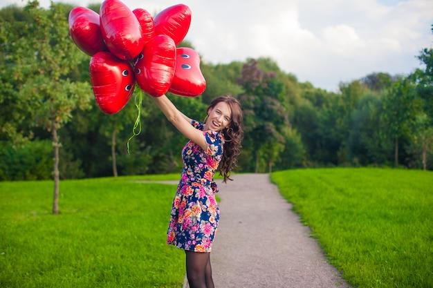 赤い風船と美しいドレスの素敵な少女は屋外楽しい時を過す