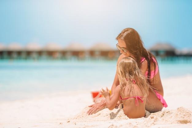ビーチで小さな娘を持つお母さん。
