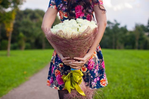 色付きのドレスの少女の手に白いバラの信じられないほど美しい大きな花束
