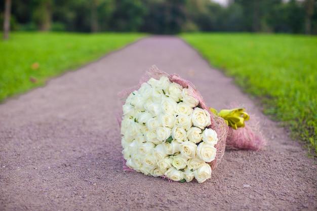 庭の砂の道の白いバラの信じられないほど美しい大きな花束