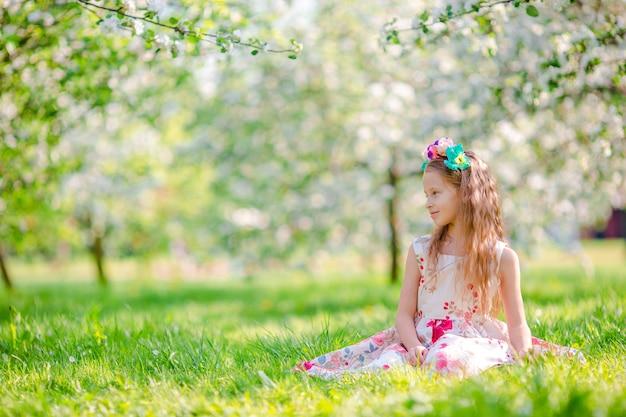 Очаровательные маленькие девочки в цветущем саду яблонь в весенний день
