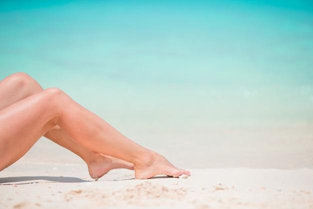 浅瀬の白い砂のビーチで女性の足