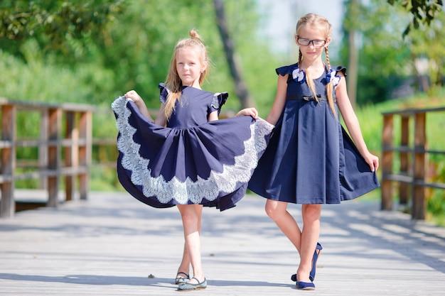 Очаровательные маленькие школьницы на открытом воздухе в теплый сентябрьский день. обратно в школу.