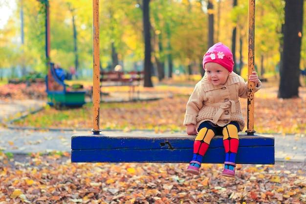 Маленькая красивая девушка весело на качелях в осеннем парке