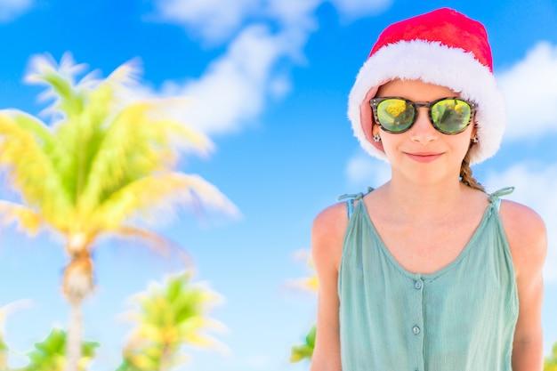 Прелестная маленькая девочка в шляпе санты во время рождественских каникул пляжа