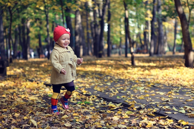 Маленькая красивая девушка гуляя в парк осени