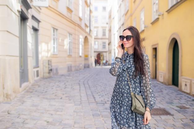 街で彼女のスマートフォンで女性が話します。