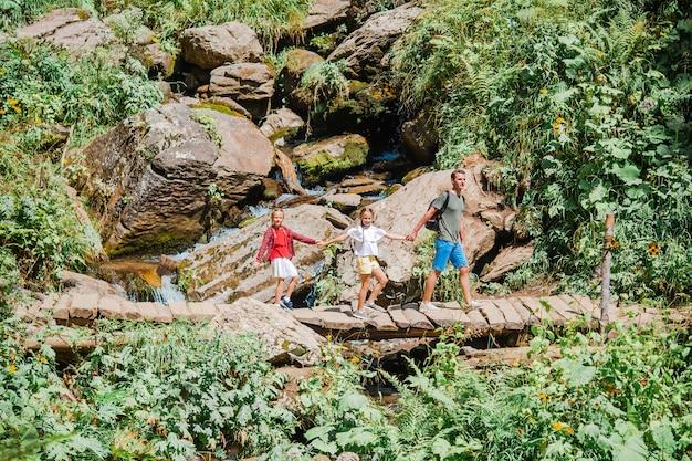 Красивые дети и счастливый человек в горах