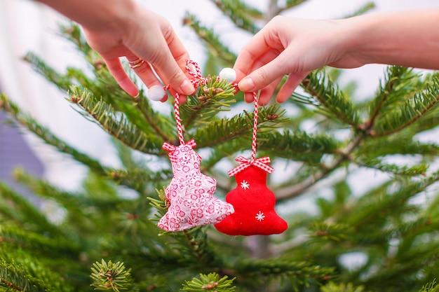 伝統的なクリスマスツリーの飾りを飾る手のクローズアップ
