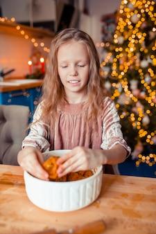 クリスマスのジンジャーブレッドのクッキーを焼くのかわいい女の子