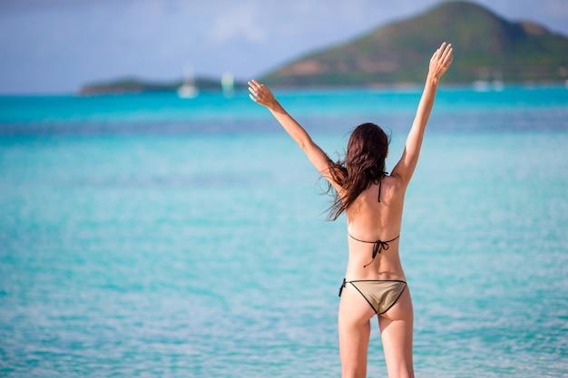 Молодая красивая женщина, развлекаясь на тропическом побережье. счастливая девушка гуляя на тропический пляж с белым песком