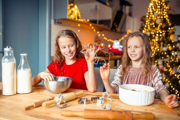 Маленькие девочки, делая рождественские пряники дома у камина в украшенной гостиной.