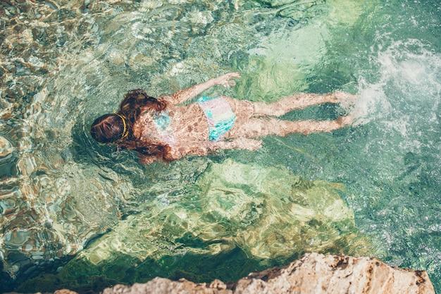 Счастливая маленькая девочка в маске для подводного плавания под водой с тропическими рыбами