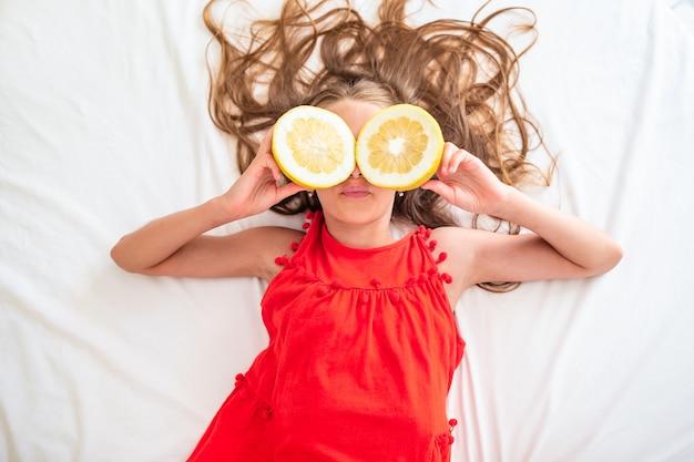 Маленькая девочка закрывает глаза половинками лимона возле глаз