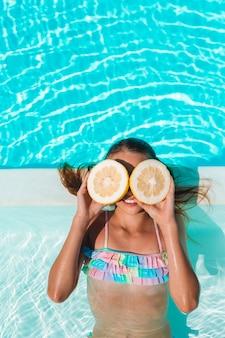 Маленькая девочка закрыла глаза половинками лимона возле глаз на фоне бассейна