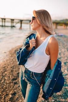 ビーチでスタイリッシュな女性のアウトドアファッションの肖像画。