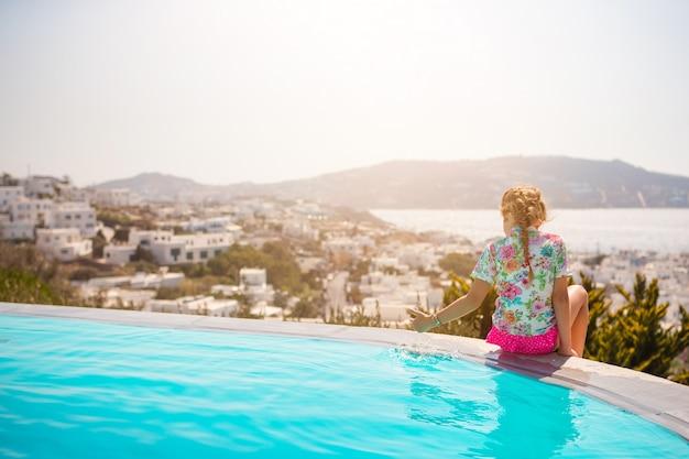 Очаровательная маленькая девочка на краю открытого бассейна