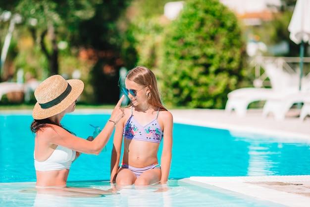 Молодая мать наносит солнцезащитный крем на нос дочери
