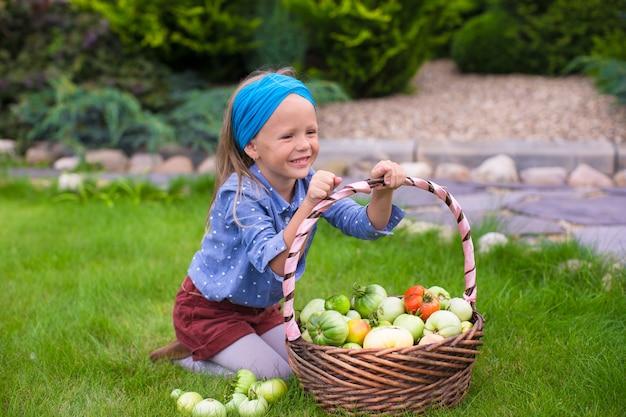 Счастливый маленькая девочка с осеннего урожая помидоров в корзинах