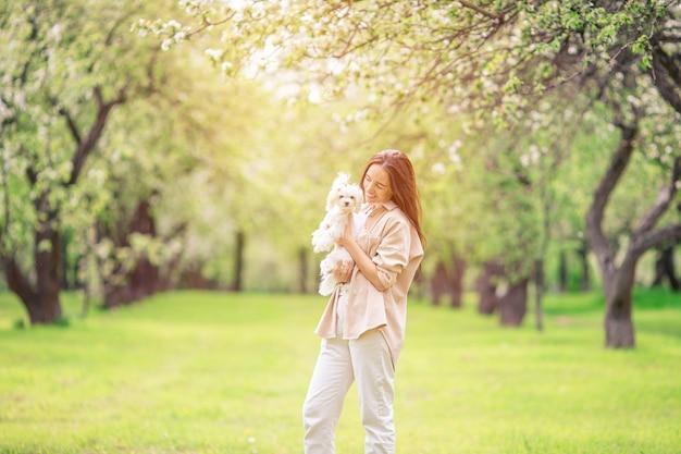 Женщина играет и обнимает щенка в парке