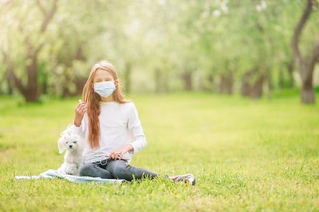 Маленькая девочка с собакой носить защитную медицинскую маску для предотвращения вирусов на открытом воздухе в парке
