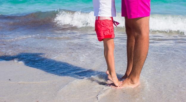 白い砂浜で彼女の父の足の上に立っている女の子