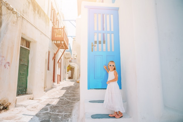 ミコノス島の古い通りの屋外のドレスの愛らしい少女。