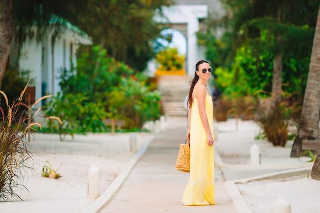 Молодая женщина во время тропического отпуска пляжа. вид сзади счастливая девушка, наслаждаясь ее праздники