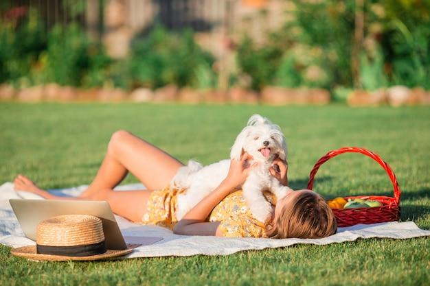 Маленькая усмехаясь девушка играя с щенком в парке